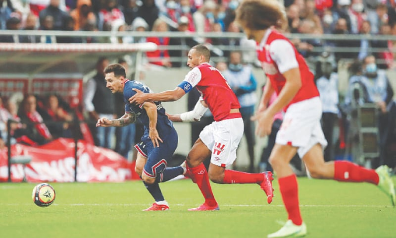 REIMS: Paris St Germain's Lionel Messi goes past Stade de Reims players during their Ligue 1 match at Stade  Auguste-Delaune.—Reuters