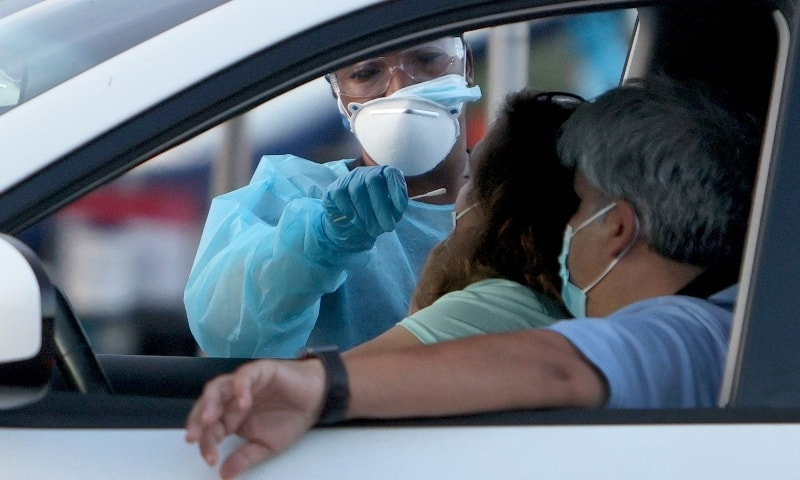 A healthcare worker at a 24-hour drive-thru site set up by Miami-Dade and Nomi Health in Tropical Park administers a Covid-19 test on August 30. — AFP