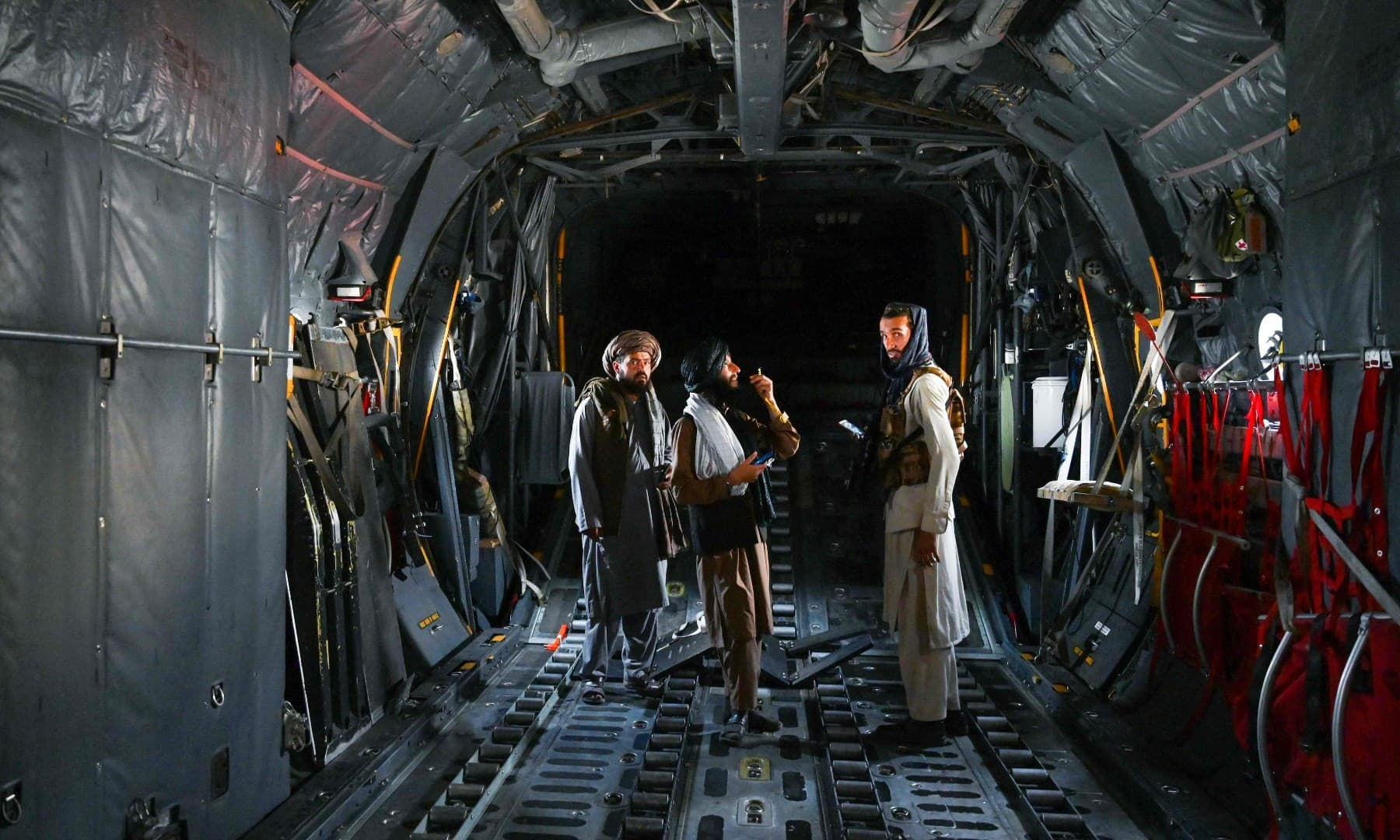 Taliban fighters stand inside an Afghan Air Force aircraft at the airport in Kabul on August 31. — AFP