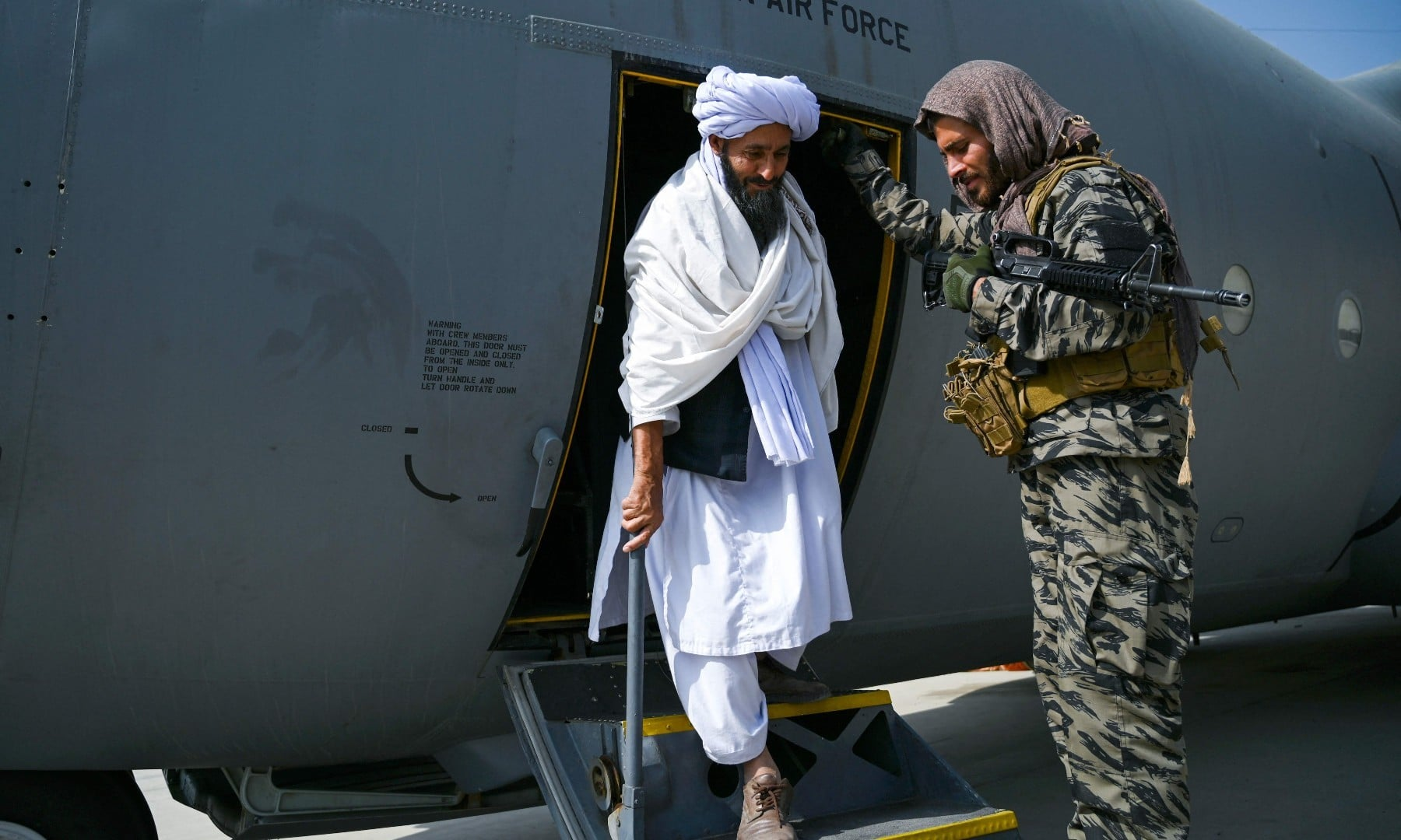 A member of the Taliban (C) walks out of an Afghan Air Force aircraft at the airport in Kabul on August 31. — AFP