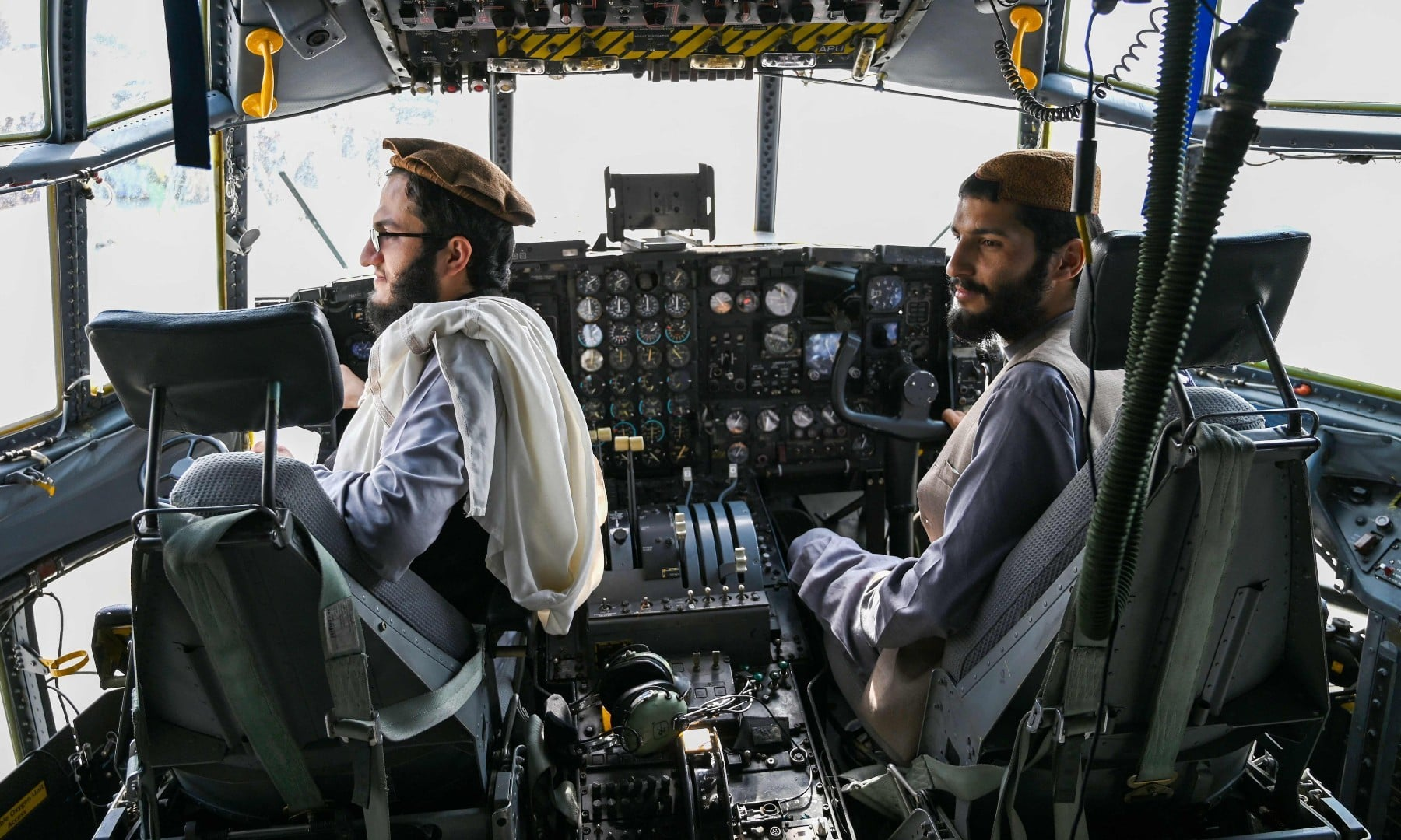 Taliban fighters sit in the cockpit of an Afghan Air Force aircraft at the airport in Kabul on August 3. — AFP