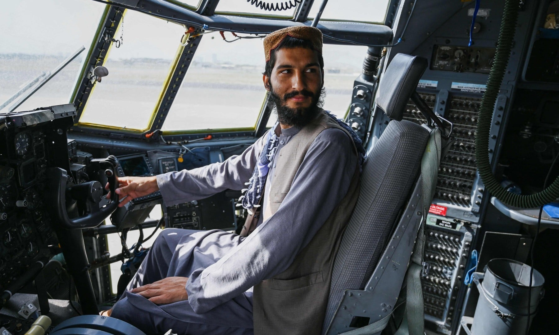 A Taliban fighter sits inside the cockpit of an Afghan Air Force aircraft at the airport in Kabul on August 31. — AFP