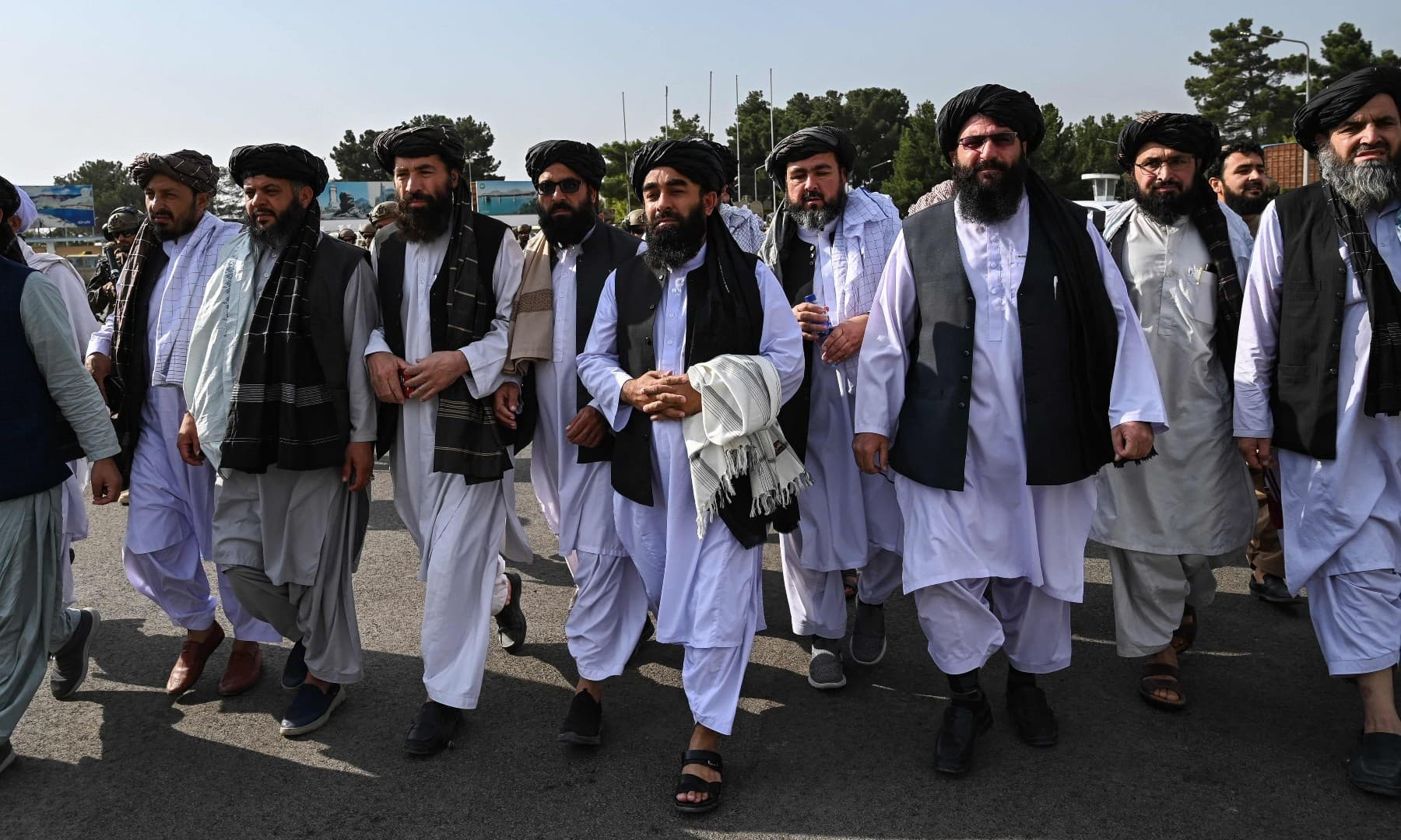 Taliban spokesman Zabihullah Mujahid (C, holding shawl) arrives as he is accompanied by officials to address a media conference at the airport in Kabul on August 31. — AFP