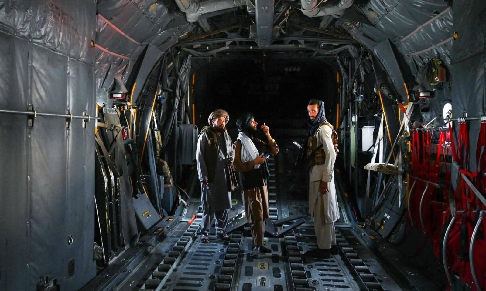 امریکی افواج کے انخلا کے بعد طالبان جنگجو طیارے میں موجود ہیں اور معائنہ کررہے ہیں — فوٹو: اے ایف پی