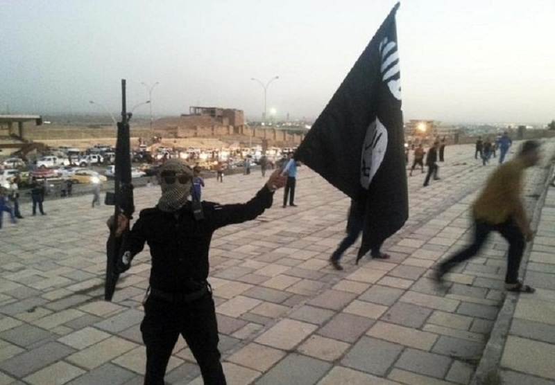 A fighter of the militant Islamic State group holds an IS flag and a weapon on a street in the city of Mosul, June 23, 2014. — Reuters