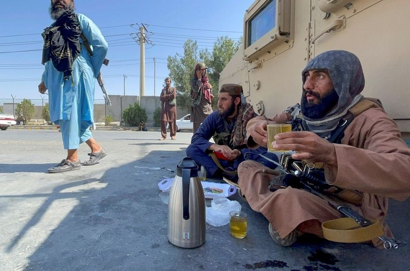 Armed Taliban men drink tea as Taliban forces block the roads around the airport after explosions in Kabul on August 27, 2021. — Reuters
