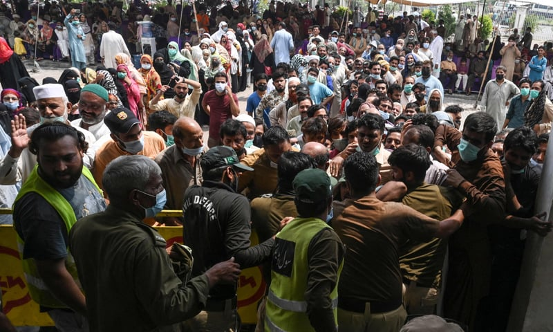 Railway employees and passengers queue to get inoculated with a dose of a Covid-19 vaccine outside a vaccination centre set up at a railway station in Lahore. — AFP