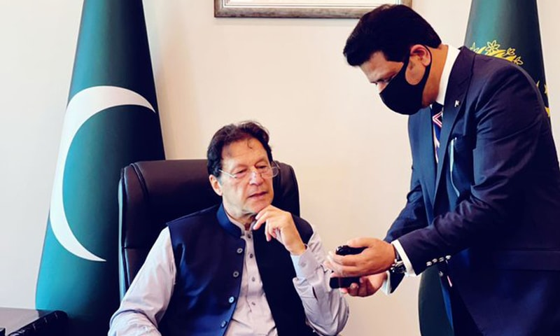 Prime Minister Imran Khan being shown the   National Database and Registration Authority's app for biometric verification on a mobile phone. — Photo courtesy PM Imran Khan Twitter