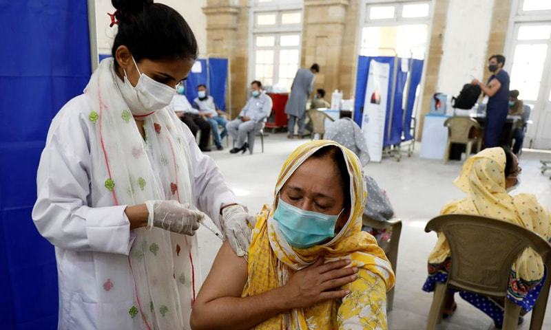 In this file photo, a woman receives a dose of Covid-19 vaccine at a vaccination centre in Karachi. — Reuters/File
