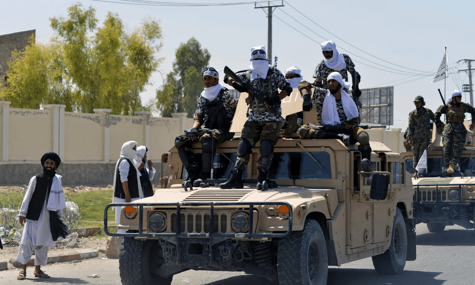 Taliban fighters atop Humvee vehicles parade along a road in Kandahar.