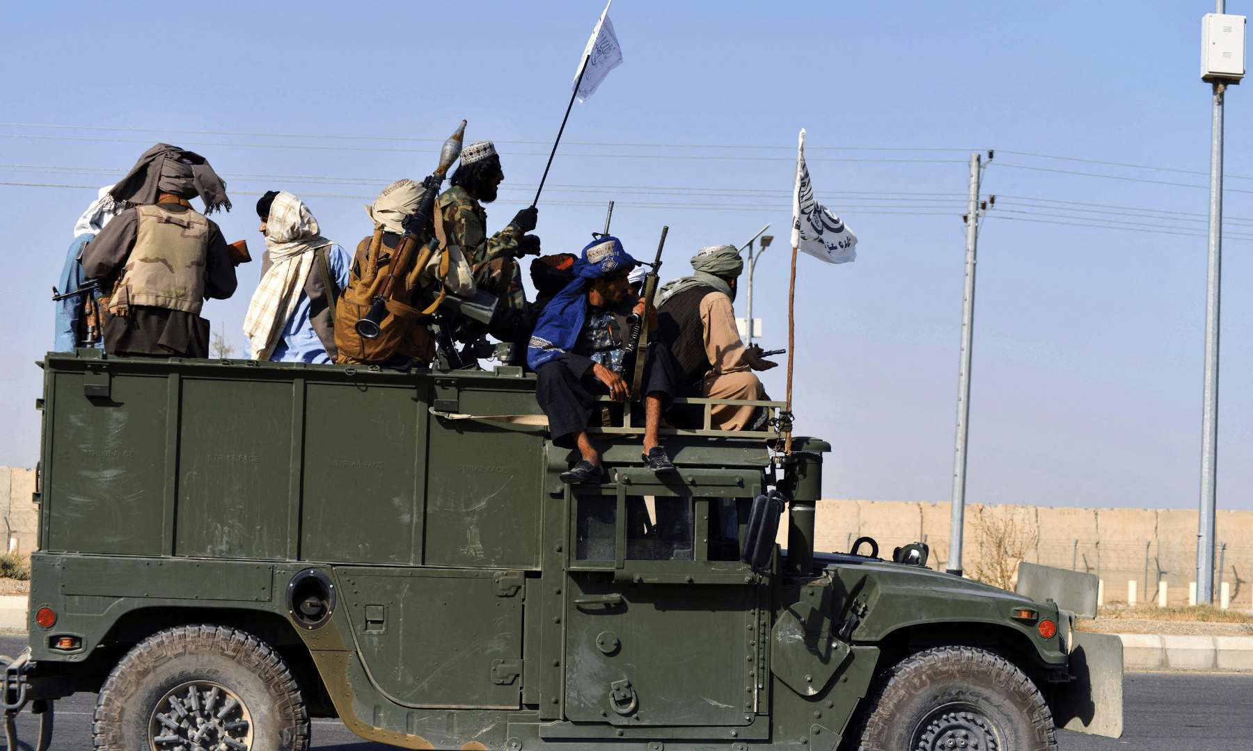 Taliban fighters stand on an armoured vehicle before parading along a road.