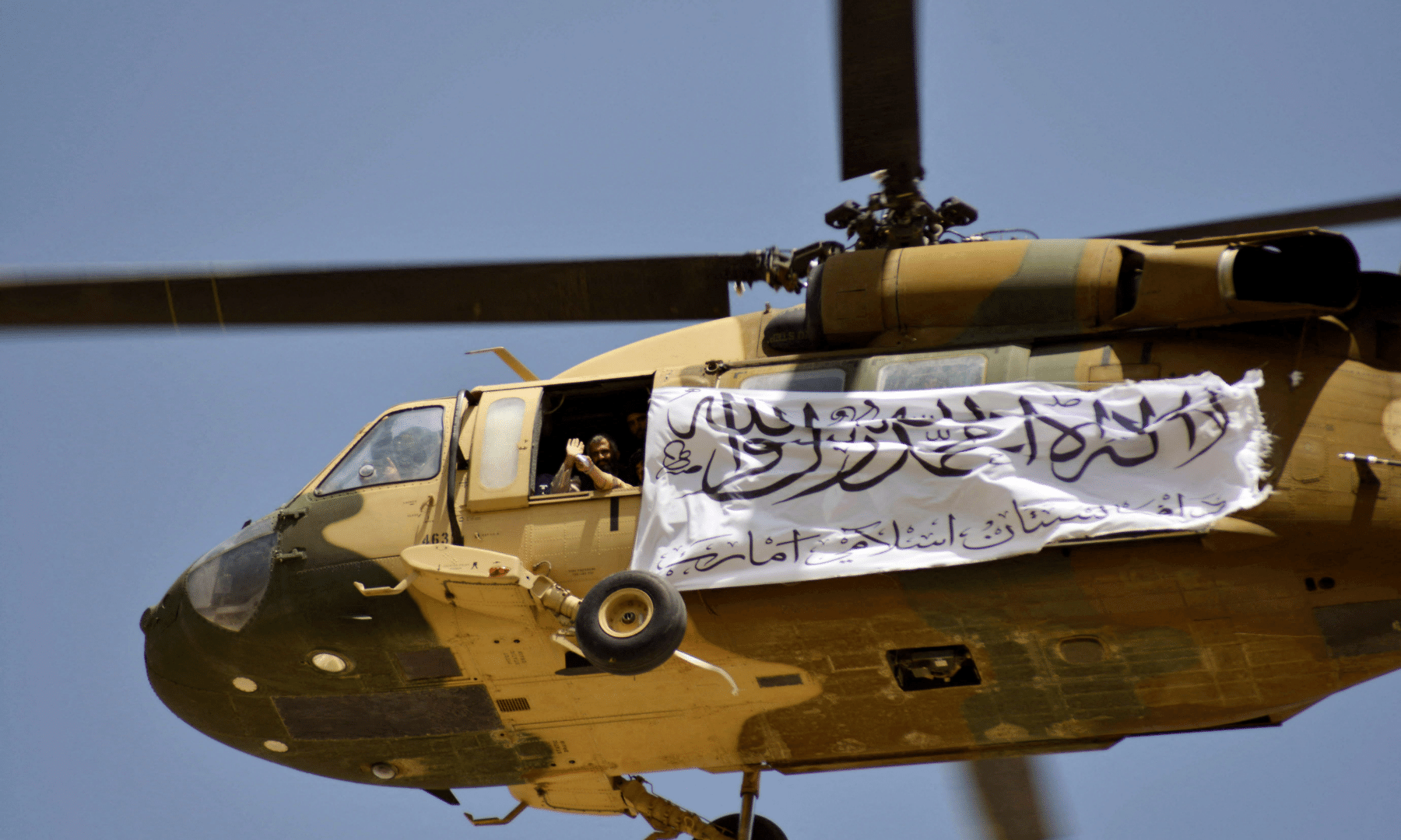 A helicopter displaying a Taliban flag flies above supporters gathered to celebrate the US withdrawal of all its troops out of Afghanistan.