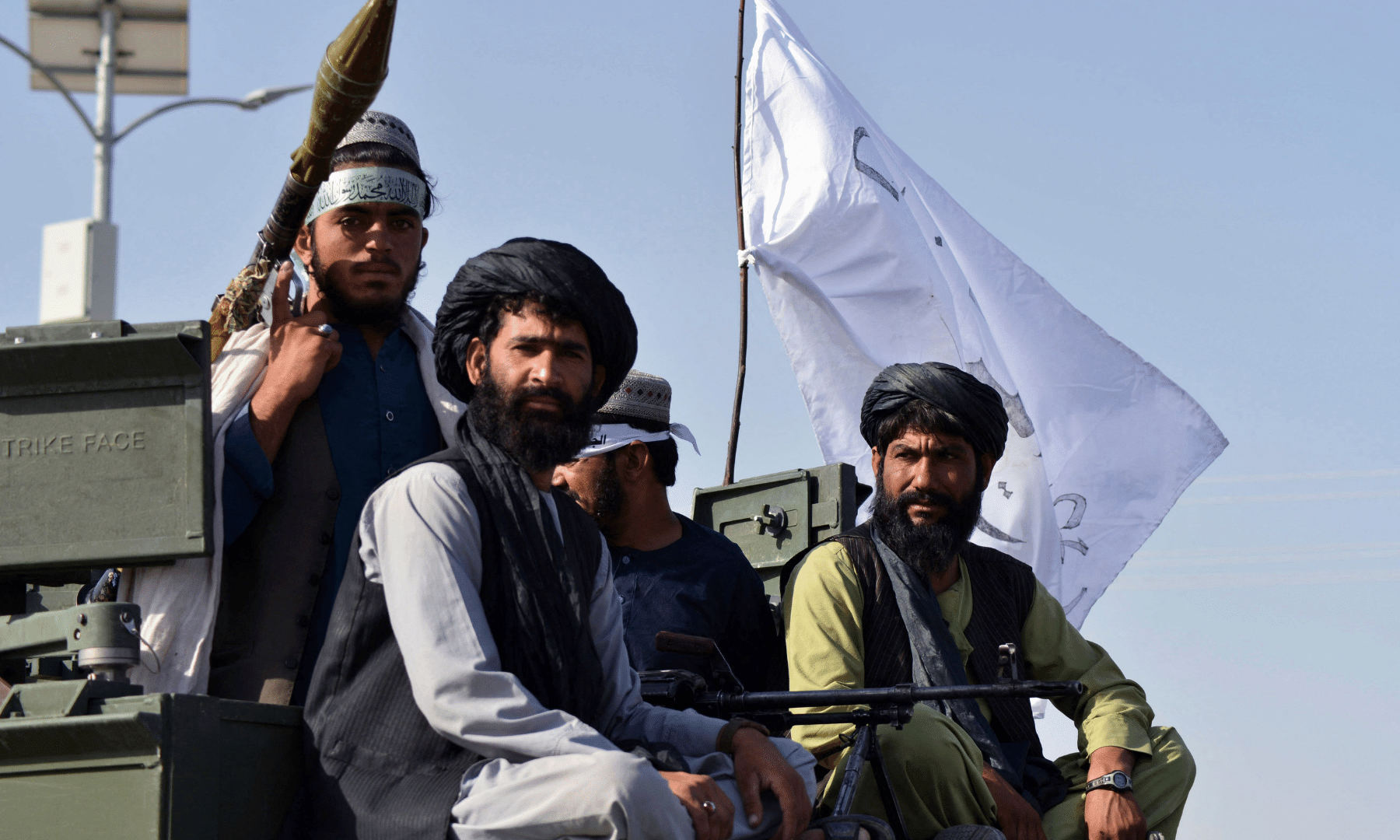 Taliban fighters stand on an armoured vehicle in Kandahar.