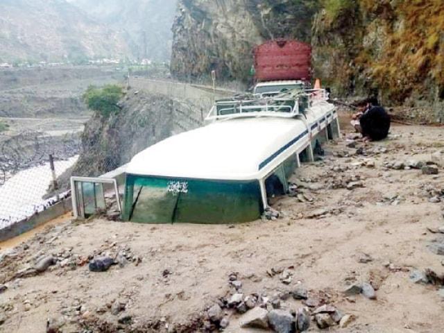 Men sit beside a coach buried under a landslide on KKH in Khushi area of Upper Kohistan on Wednesday. — Dawn