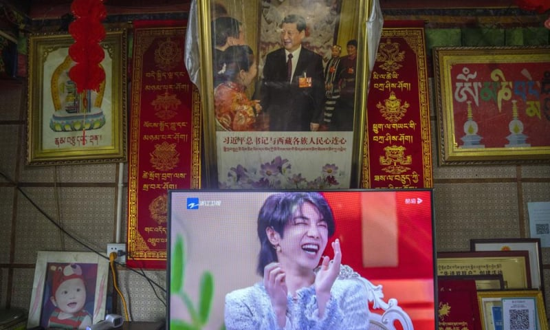 A television shows a broadcast of a Chinese talk show programme as it sits beneath a photo of Chinese President Xi Jinping in a home converted into a tourist homestay in Zhaxigang village near Nyingchi in western China's Tibet Autonomous Region on June 4. — AP/File
