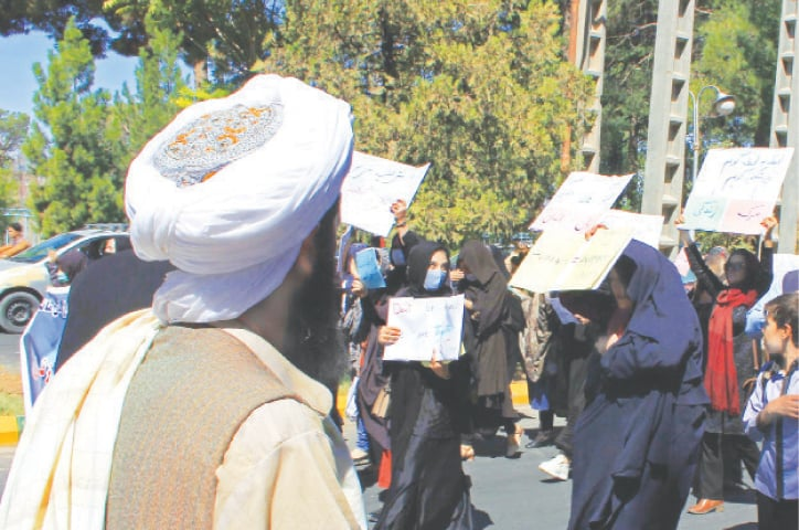 Herat: A member of the Taliban watches as Afghan women hold placards during a protest on Thursday.—AFP