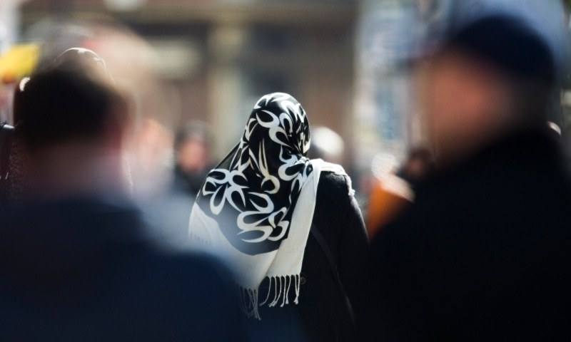 In this file photo, a woman with a headscarf walks between other people on a street at the district Neukoelln in Berlin, Germany. — AP/File