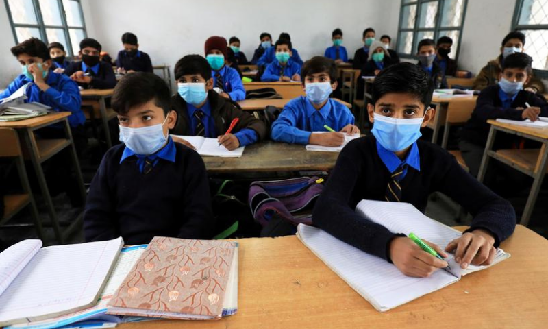 In this file photo, students wear protective masks as they attend a class at school as the outbreak of the coronavirus continues, in Peshawar. — Reuters