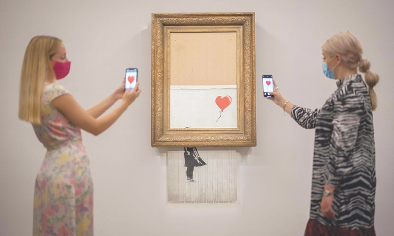LONDON: Two women pose by Love is the Bin by British street artist Banksy at Sotheby's auction house on Friday.—AFP