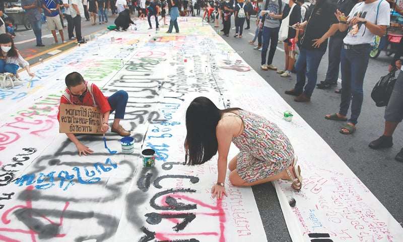 BANGKOK: Protesters write on a poster during a rally calling for Thai Prime Minister Prayuth Chan-ocha's resignation.—Reuters