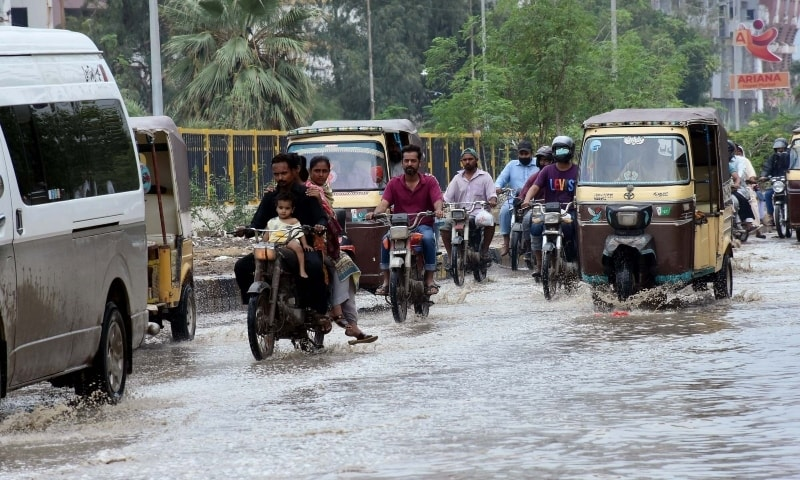 Commuters wade through rainwater in North Nazimabad after rainfall lashes Karachi on September 4. — PPI
