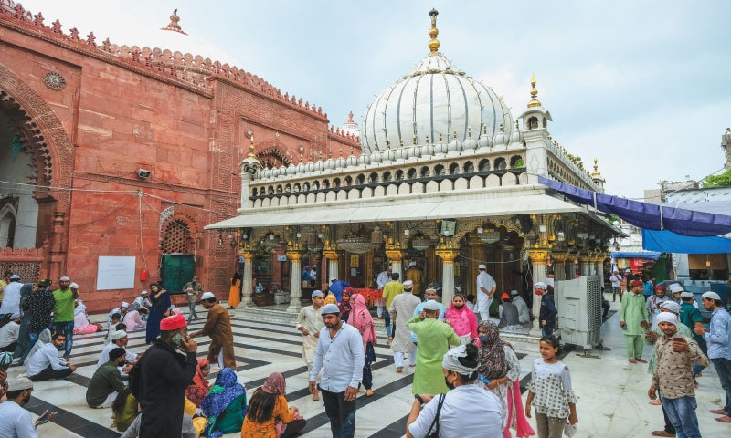 Thronging with devotees, the saint's dargah with its white, onion dome in Delhi