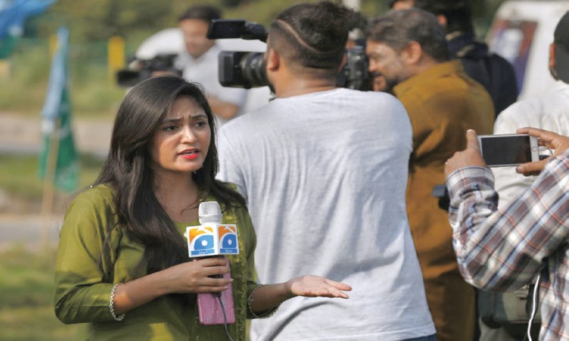 A journalist from a local tv channel reports live from a political rally in Islamabad, 2020 | AP