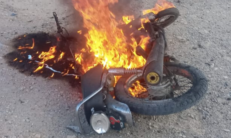 A burning motorcycle is seen at the site of the attack on Quetta's Mastung Road on Sunday. — Photo by author