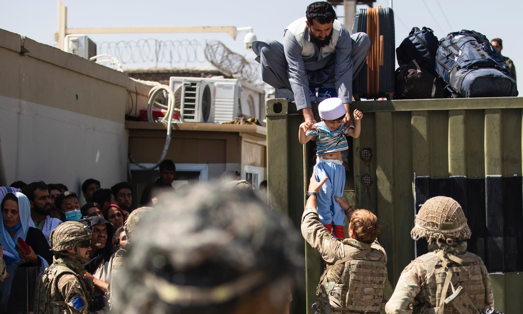 An Afghan man hands his child to a British Paratrooper assigned to 2nd Battalion, Parachute Regiment while a member of 1st Brigade Combat Team, 82nd Airborne Division conducts security at Hamid Karzai International Airport in Kabul, Afghanistan on August 26, 2021. — AP