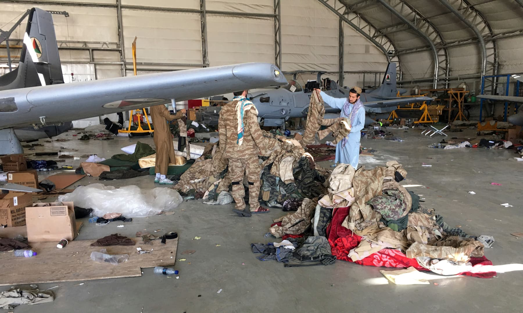 Taliban fighters collect military clothes near damaged Afghan military aircraft after the Taliban's takeover inside the Hamid Karzai International Airport in Kabul, Afghanistan on September 5, 2021. — AP
