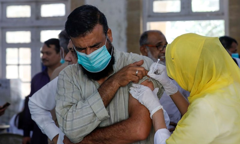 In this file photo, a man receives a dose of a Covid-19 vaccine at a vaccination center in Karachi. — Reuters/File