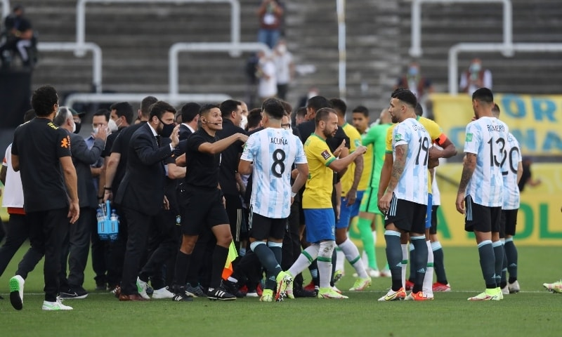 Players and officials are seen on the pitch as play is interrupted after Brazilian health officials objected to the participation of three Argentine players they say broke quarantine rules. — Reuters