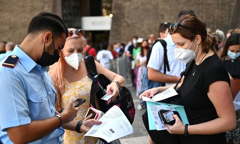 In this file photo taken on August 6, 2021 visitors show their UE digital Covid-19 certificate for scanning before entering the Vatican Museums. — AFP