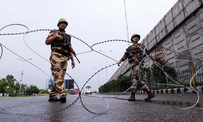 In this file photo, Indian security personnel stand guard at a roadblock in occupied Kashmir. — AFP/File