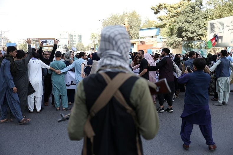 A Taliban soldier stands in front of protesters during the protest in Kabul on Tuesday.  — WANA via Reuters