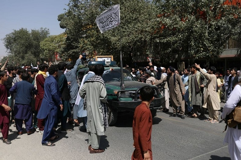 Protesters gather around a car with the Taliban flag raised atop it during protest in Kabul on Tuesday. — WANA (West Asia News Agency) via Reuters