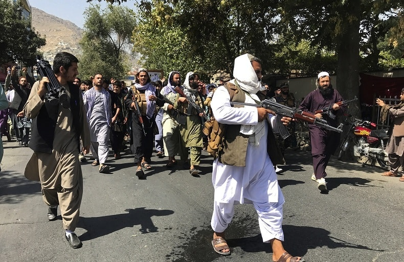 Taliban soldiers walk towards Afghans shouting slogans, during the demonstration, near the Pakistan embassy in Kabul on Tuesday. — AP