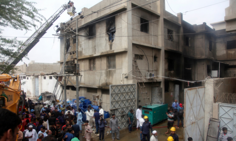 Rescue workers search bodies at the site of a burnt chemical factory, in Karachi, on Aug 27. — AP/File