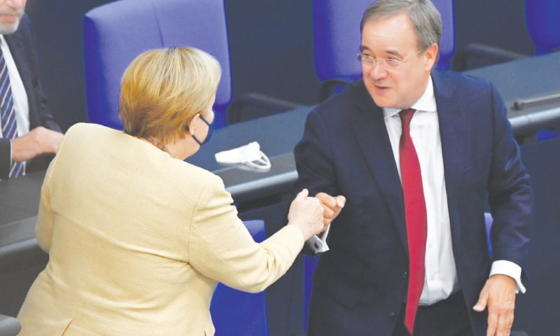 GERMAN Chancellor Angela Merkel bumps fists with Armin Laschet, tipped to succeed her as the Christian Democratic Union's chief next month, during a session of parliament's lower house.—AFP