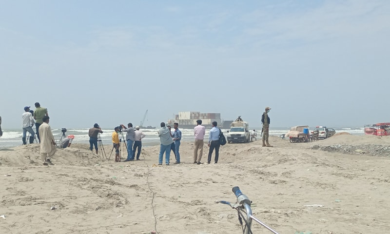 Citizens watch as the beached cargo ship MV Heng Tong 77 is freed at Karachi's Seaview beach. — Photo by author