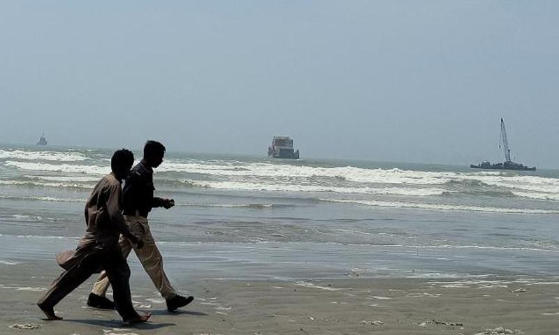 Two men walk at Karachi's Seaview beach as cargo ship MV Heng Tong 77 leaves. — Photo by author
