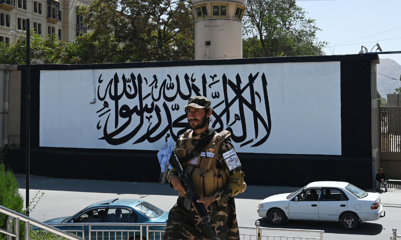 """A member of the Taliban Fateh fighter, a """"special forces"""" unit, stands guard outside the US embassy in Afghanistan displaying a Taliban flag in the outer concrete wall in Kabul on Wednesday. — AFP"""
