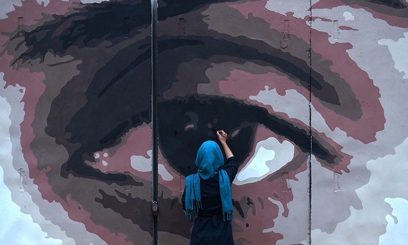 In this file photo, an Afghan artist paints the design of the eyes of a woman on a barrier wall at the presidential palace in Kabul. ─ AFP/File