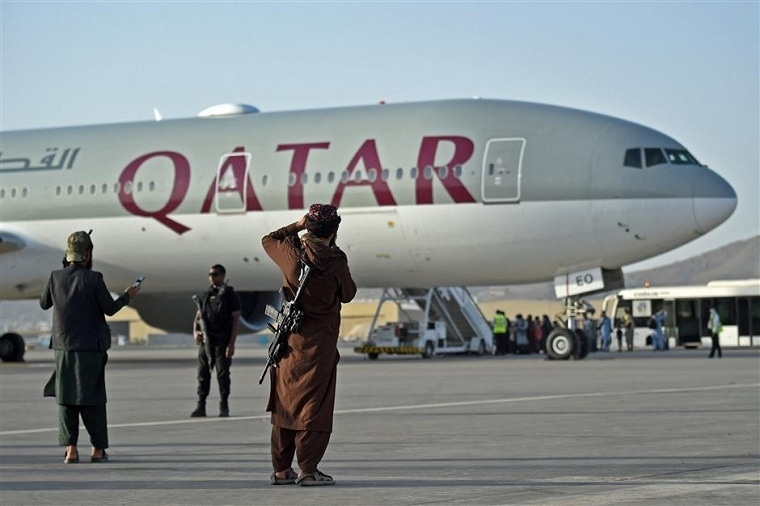 A Qatari security personnel and Taliban fighters stand guard as passengers board a Qatar Airways aircraft at the airport in Kabul on September 9. — AFP