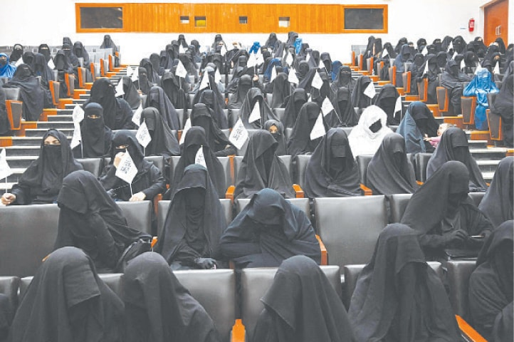 Kabul: Girls hold Taliban flags as they listen to a speaker at the Shaheed Rabbani Education University on Saturday. Afghanistan marked the 20th anniversary of 9/11 attacks in muted fashion on Saturday with the Taliban firmly in charge, two decades after being ousted from power. Hundreds of fully veiled women held a rally at the university to express support for the Taliban. — AFP