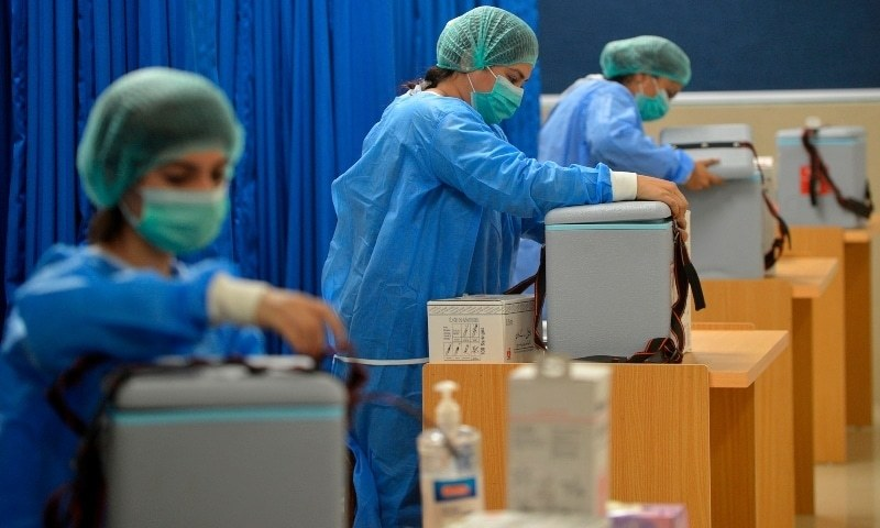 Medical attendants prepare to vaccinate health workers at a vaccination centre in Karachi. — AFP/File