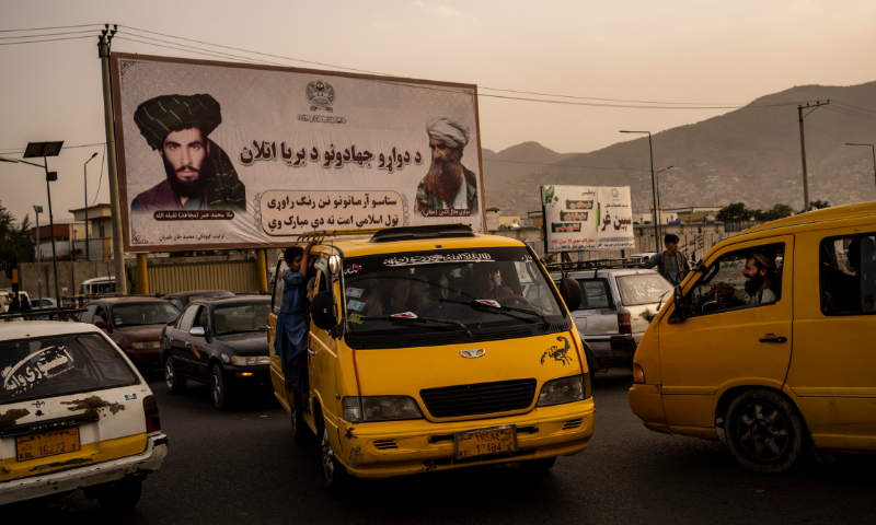 KABUL: Vehicles drive past a mural paying homage to the late Taliban founder Mullah Mohammad Omar and the late founder of the Haqqani network, Jalaluddin Haqqani, on Saturday. — AP