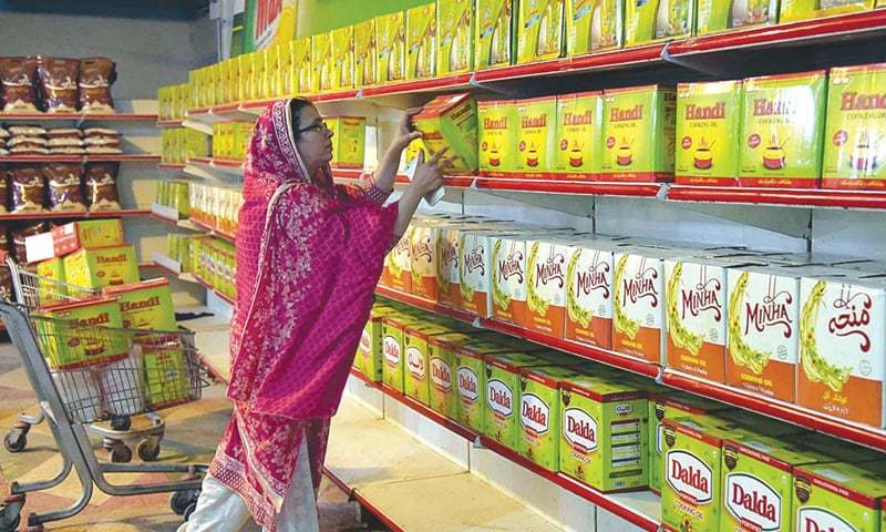 A woman lifts a box of ghee from a supermarket. — Dawn/File