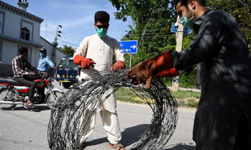 Plainclothes policemen seal off a street with barbed wire in a neighbourhood after some residents tested positive for Covid-19 in Islamabad. — AFP/File