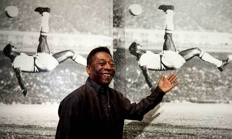 """Brazilian football legend Pele poses for photographers in front of a painting entitled """"Pele, Bicycle Kick"""" by artist Russell at the exhibition """"Pele: Art, Life, Football"""" at the Halcyon Gallery in London. — AFP/File"""